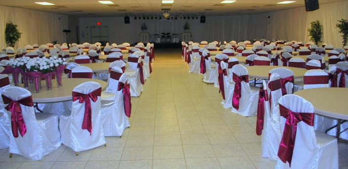 A beautiful event that features burgundy chair sashes as well as white chair covers.]